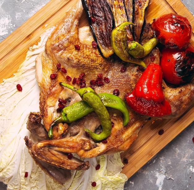 Pollo e verdure grigliati sul primo piano del bordo di legno. vista orizzontale dall'alto Foto Gratuite