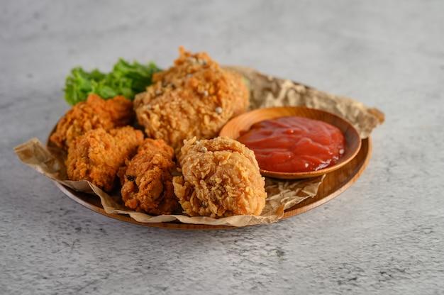 Pollo fritto croccante su un piatto con salsa al pomodoro Foto Gratuite
