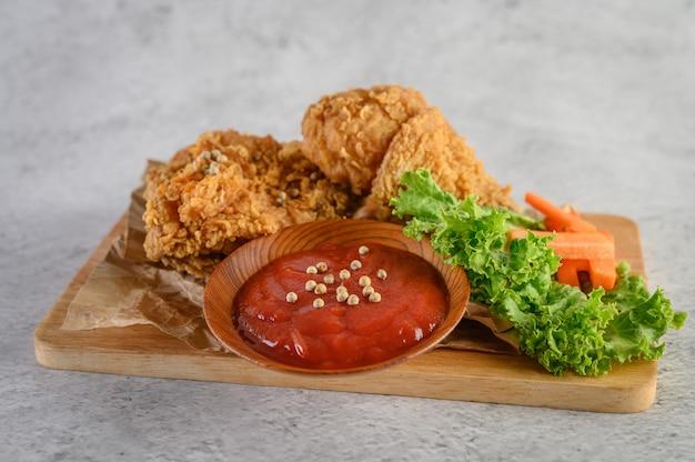 Pollo fritto croccante su un tagliere con salsa di pomodoro Foto Gratuite