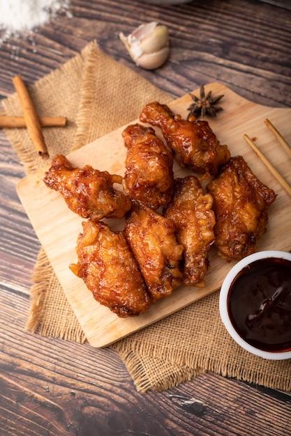 Pollo fritto del barbecue coreano caldo e piccante sul tagliere di legno Foto Premium