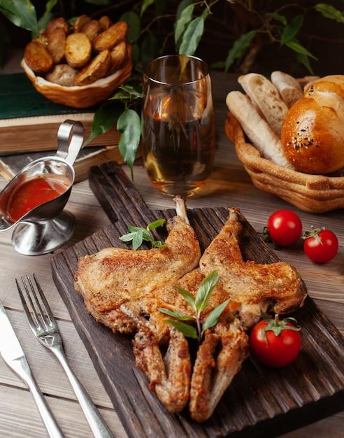 Pollo intero alla griglia con salsa di pomodoro ed erbe su tavola di legno Foto Gratuite