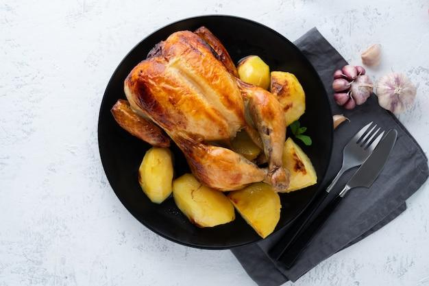 Pollo intero alla griglia nel piatto sul tavolo bianco, carne al forno con patate. vista dall'alto, copia spazio Foto Premium