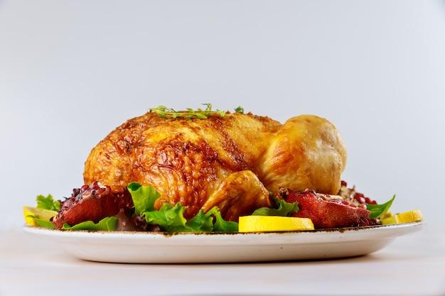 Pollo intero arrosto sul piatto con insalata e melograno Foto Premium