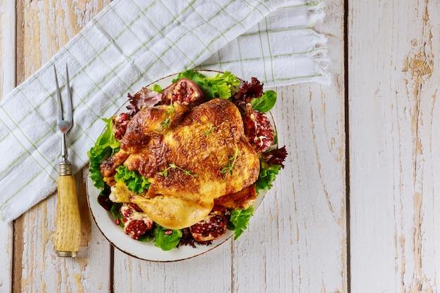 Pollo intero arrosto sul piatto con insalata, melograno e forchetta Foto Premium