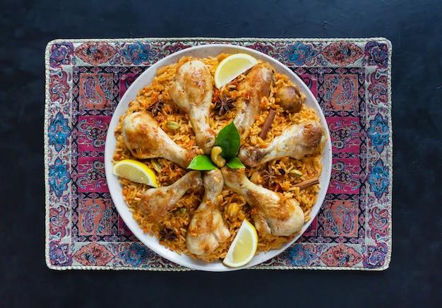 Pollo mandi con date su un tavolo nero. cucina araba. vista dall'alto. Foto Premium