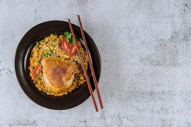 Pollo sano del riso fritto dell'alimento con i pomodori e prezzemolo con le bacchette Foto Premium