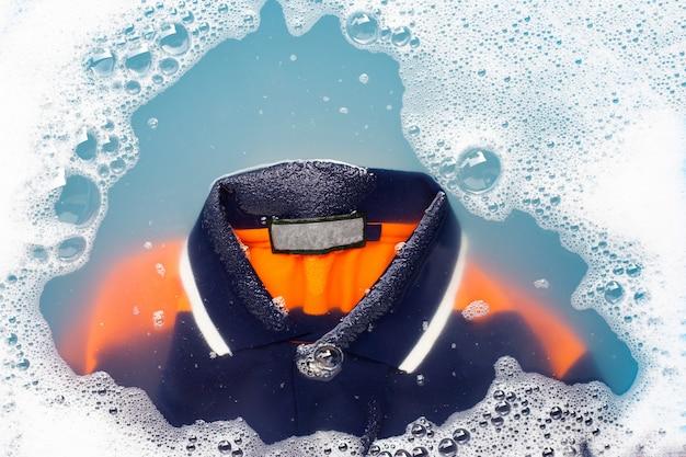 Polo impregnata di detergente in polvere per dissoluzione dell'acqua. concetto di lavanderia Foto Premium
