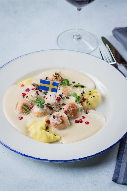 Polpette con patate bollite, salsa e frutti di bosco decorati dalla bandiera svedese Foto Premium