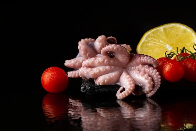 Polpo vista frontale con limone e pomodori Foto Gratuite