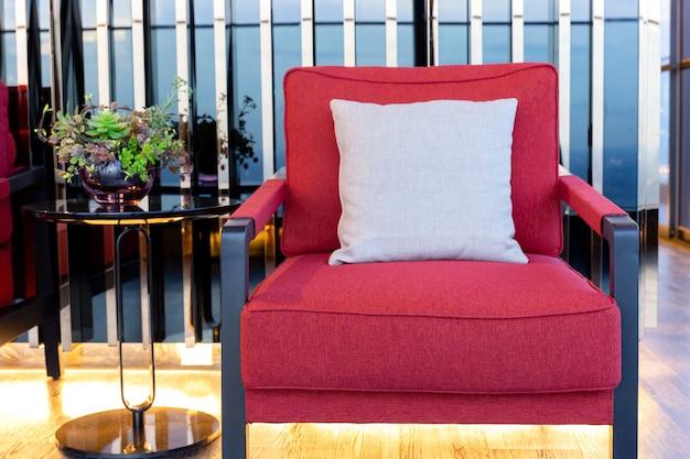 Poltrona rossa del cotone del primo piano con il cuscino vicino al tavolino da salotto nero in salone. Foto Premium