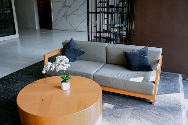 Poltrona sul tappeto accanto alla panchina con piante in interno loft bianco con divano in legno. Foto Premium
