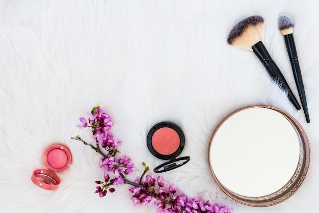 Polvere compatta rosa con rametto di fiori; pennelli specchio e trucco su sfondo di pelliccia bianca Foto Gratuite