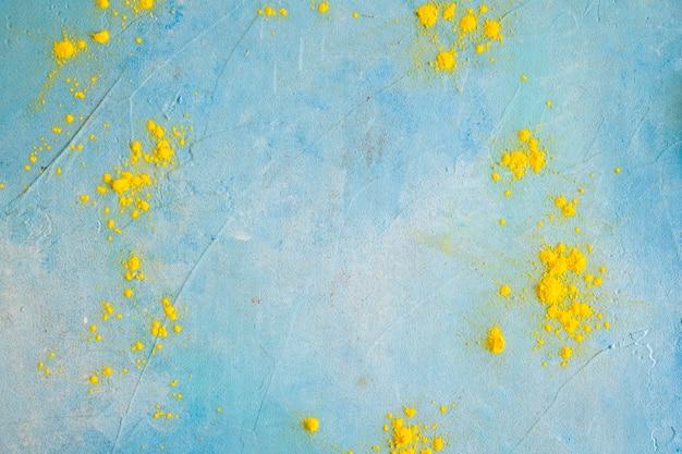 Polvere di colore giallo sulla parete blu dipinta Foto Gratuite