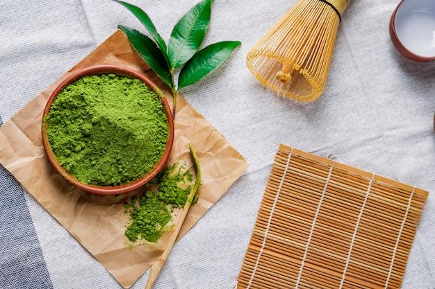 Polvere di tè verde con foglia in un piatto di ceramica sul tavolo, frusta giapponese fatta di bambù per la cerimonia del tè matcha Foto Premium