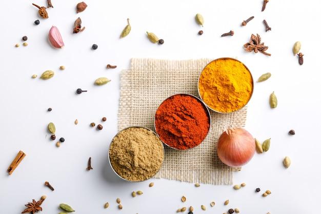 Polvere rossa dei peperoncini rossi delle spezie variopinte indiane, polvere della curcuma, polvere del coriandolo sulla tavola bianca Foto Premium