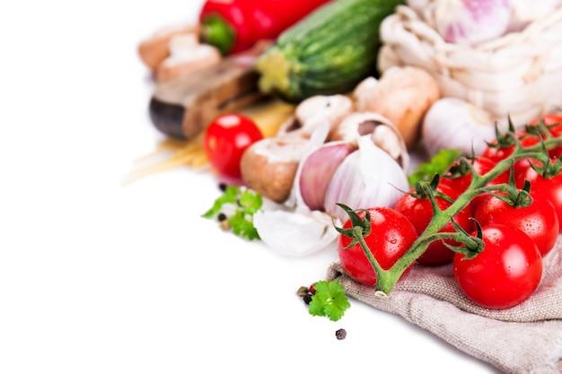 Pomodori, aglio e zucchine allineati su uno sfondo bianco Foto Gratuite