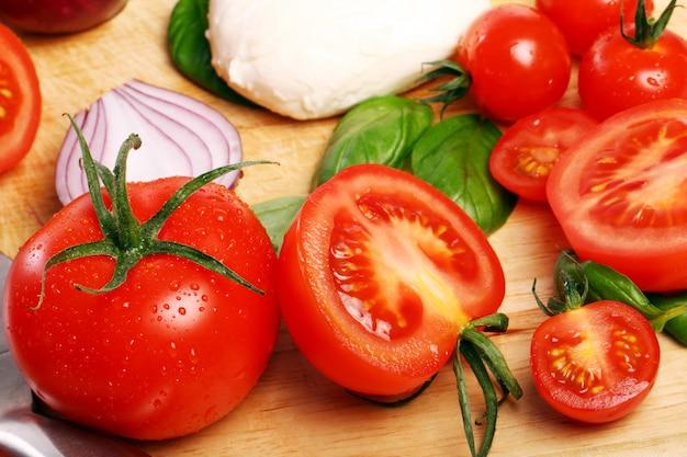 Pomodori, basilico e mozzarella su tavola di legno Foto Gratuite