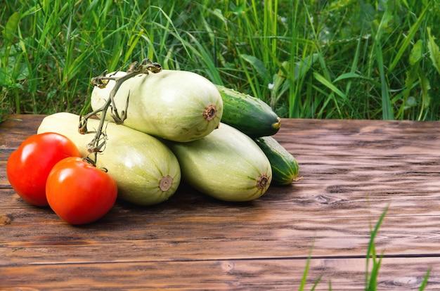 Pomodori, cetrioli e zucca su tavole di legno con erba verde sullo sfondo. Foto Premium
