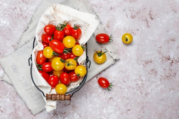 Pomodori ciliegia di vari colori, pomodori ciliegia gialli e rossi in un canestro su fondo leggero Foto Gratuite