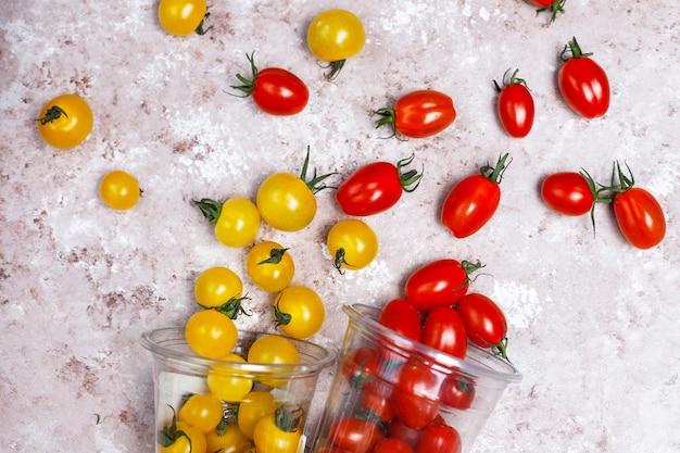 Pomodori ciliegia di vari colori, pomodori ciliegia gialli e rossi su sfondo chiaro Foto Gratuite
