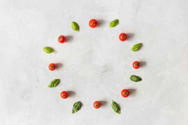 Pomodori ciliegia e foglie di basilico disposte in cornice circolare su sfondo bianco strutturato Foto Gratuite