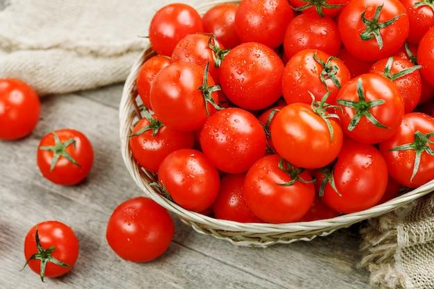 Pomodori ciliegia maturi e succosi con gocce di umidità in un cestino di vimini. vecchio tavolo di legno, attorno alla tela di tela Foto Premium