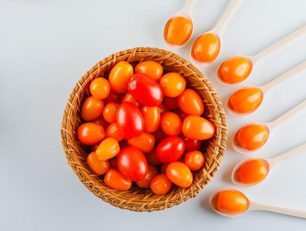 Pomodori colorati in cucchiai e cestino di legno. disteso. Foto Gratuite