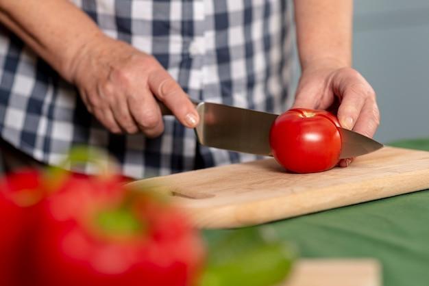 Pomodori di taglio della donna più anziana del primo piano Foto Gratuite