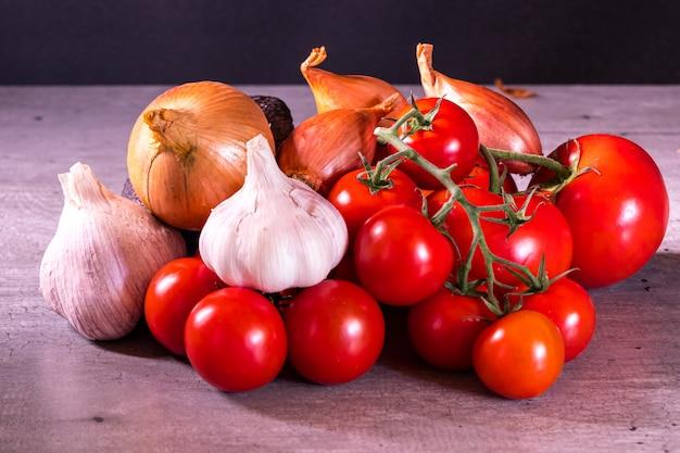 Pomodori e cipolle di aglio assortiti per un manifesto della decorazione della cucina Foto Premium