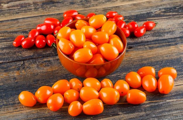 Pomodori freschi in una vista dell'angolo alto della ciotola su una tavola di legno Foto Gratuite