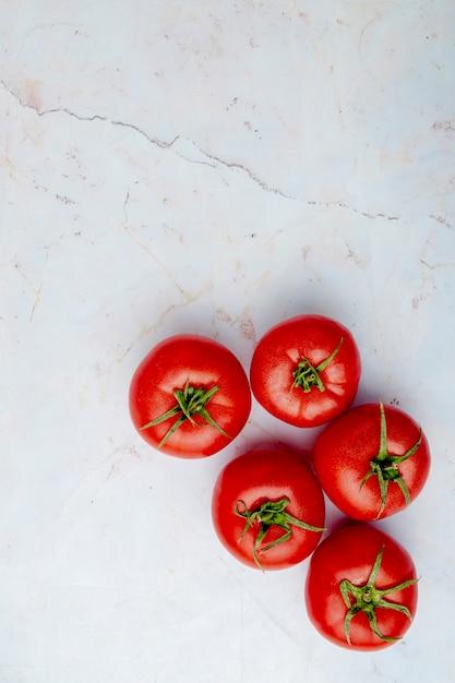 Pomodori interi su superficie bianca Foto Gratuite