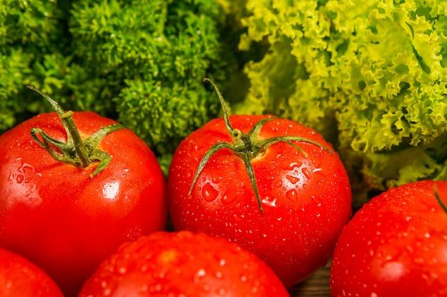 Pomodori maturi freschi su una tavola di legno con un'insalata verde Foto Premium
