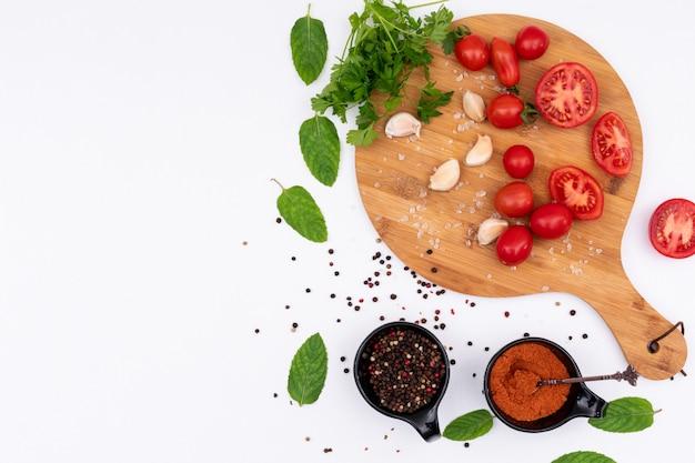 Pomodori sul tagliere di legno con la vista superiore delle spezie su superficie bianca Foto Gratuite