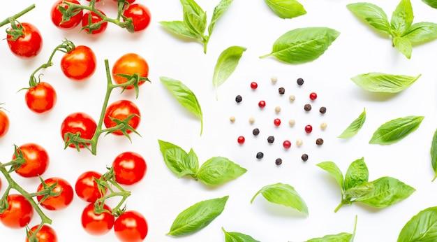 Pomodorini freschi con foglie di basilico e diversi tipi di grani di pepe Foto Premium