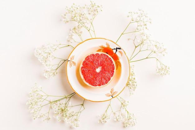 Pompelmo diviso in due sul piatto ceramico decorato con i fiori del respiro del bambino su fondo bianco Foto Gratuite