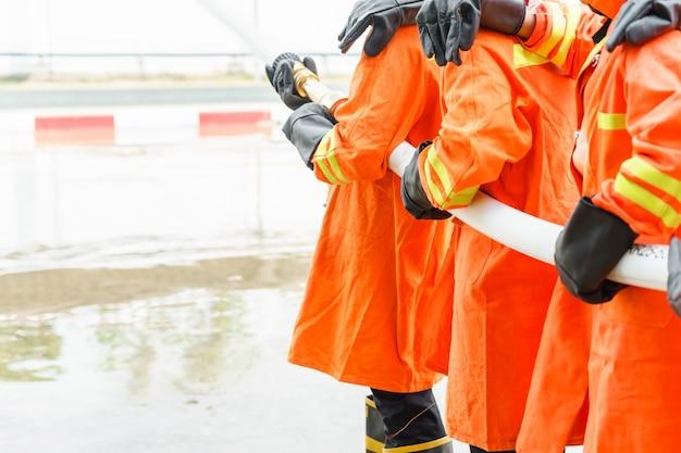 Pompiere che utilizza estintore e acqua dal tubo per la lotta antincendio Foto Premium