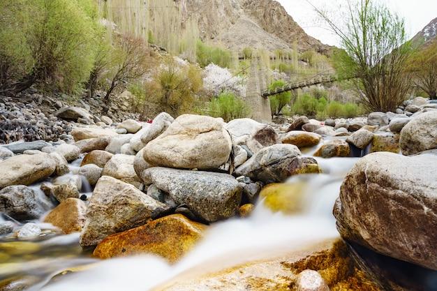 Ponte di legno di turtuk con acqua che scorre sotto nel villaggio di turtuk. leh ladakh, india Foto Premium