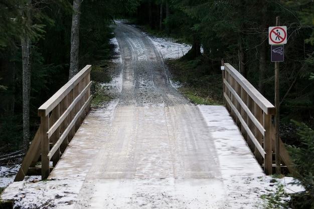 Ponte di legno nella foresta. strada coperta di neve Foto Premium