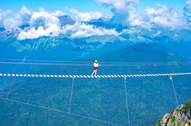 Ponte sospeso in legno sul precipizio. vacanze estreme Foto Premium