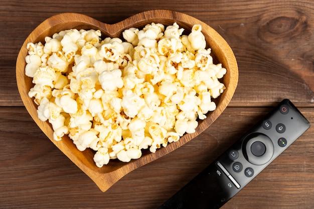 Popcorn a forma di cuore in una ciotola di legno e un telecomando della televisione su una tavola di legno Foto Premium