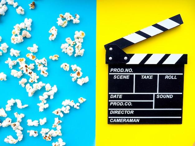 Popcorn, bicchieri per cinema e ciak su sfondo colorato. Foto Premium
