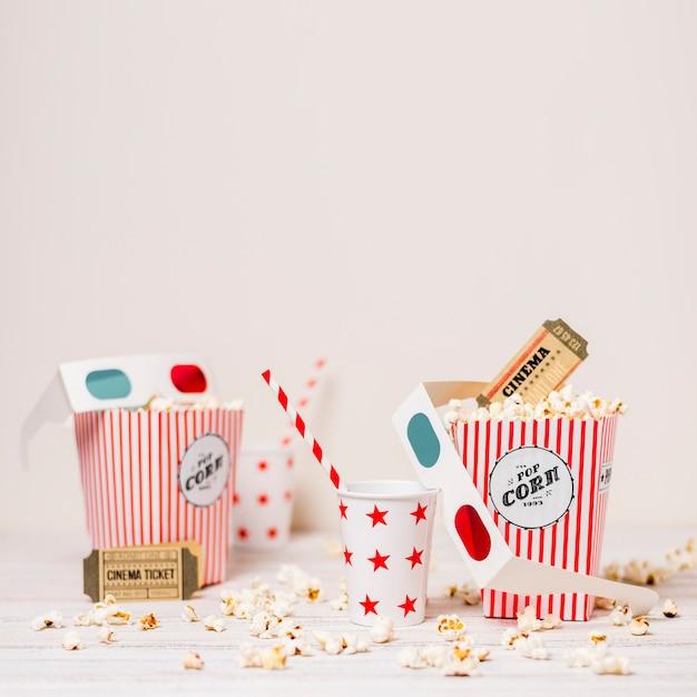 Popcorn; biglietto del cinema; vetro usa e getta con cannuccia e scatola di popcorn sul tavolo su sfondo bianco Foto Gratuite