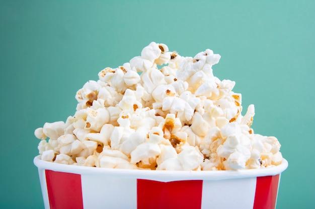 Popcorn fresco irascibile in tazza di carta rossa e bianca o tazza di carta a strisce osservata da sopra isolata su verde Foto Premium