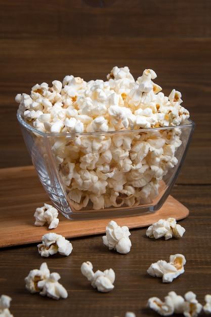 Popcorn in ciotola di vetro su legno Foto Premium