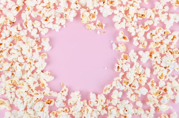 Popcorn sparsi su uno sfondo rosa pastello Foto Premium