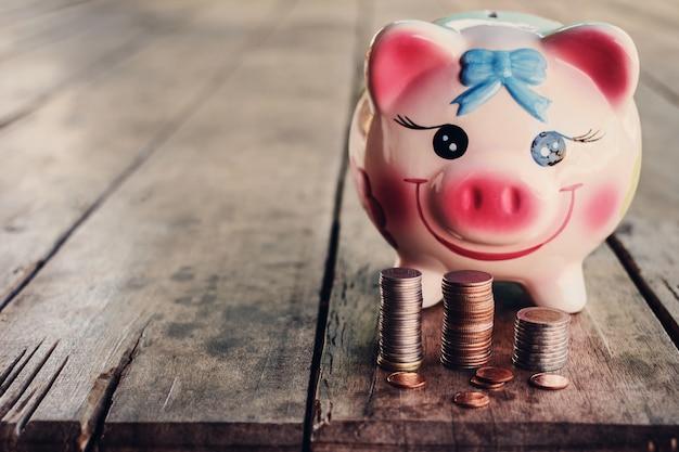 Porcellino salvadanaio carino con moneta sul vecchio tavolo di legno Foto Premium