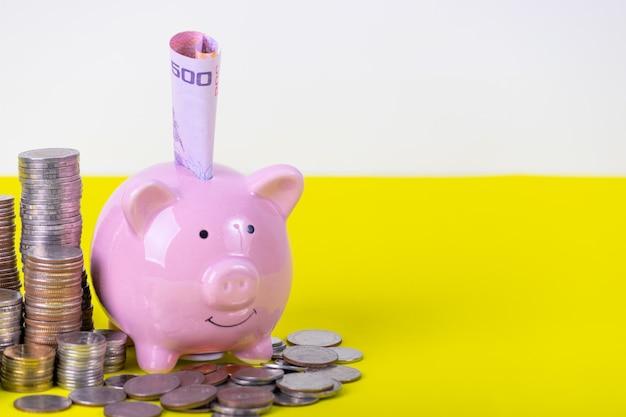 Porcellino salvadanaio con la pila di moneta sul tavolo giallo. concetto di denaro finanziario o di risparmio. Foto Premium