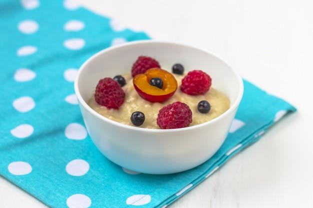 Porridge colazione sana per i bambini. ciotola di alimenti per bambini su un tessuto. il concetto di corretta alimentazione e cibo sano. Foto Premium