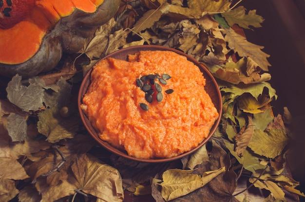 Porridge di zucca con semi sul tavolo di legno Foto Premium