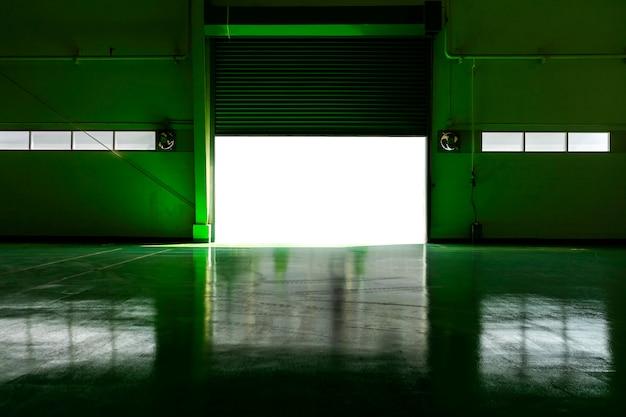 Porta della fabbrica di metallo e area verde del pavimento con la luce del sole. Foto Premium